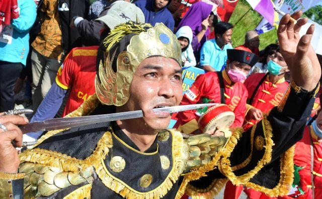 Indonezijec na paradi festivala Cap Go Meh v Singkawangu izvaja prebadanje meča skozi lice. Kitajski Indonezijci s festivalom označijo konec lunarnega novega leta. Foto Daddy Cavalero Afp