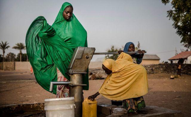 V begunskem taborišču Malkohi v nigerijskem mestu Jimeta ženske iz vodnjaka črpajo vodo. Malkohi je tabor za vse, ki so zapustili svoje domove, ko so uporniki Boko Harama okupirali severovzhodni del države. FOTO: Luis Tato/AFP