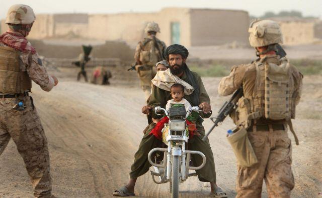 Večerna patrulja marincev zaustavlja in pregleduje domačina na cestni kontrolni točki v okro�ju Garm�ir, v provinci Helmand v Afaganistanu. FOTO: Jure Eržen