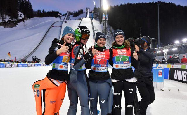 Slovenske skakalke (na fotografiji z leve Nika Križnar, Urša Bogataj, Špela Rogelj in Jerneja Brecl) so imele mešane občutke po četrtem mestu na zgodovinski prvi ekipni tekmi na nordijskih SP. FOTO: AFP