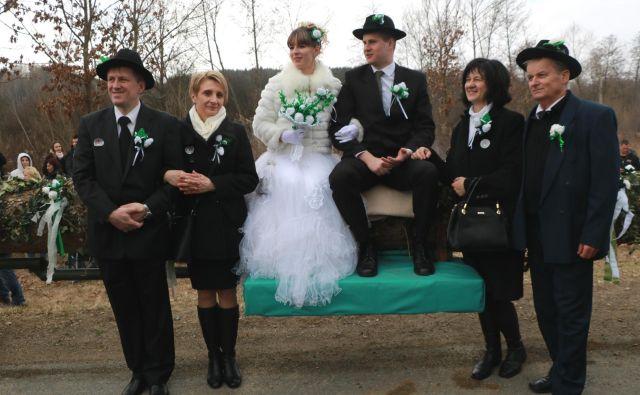 """Ženin in nevesta sta se v spremstvu """"staršev"""" v vas peljala na plohu. FOTO: Jože Pojbič/Delo"""