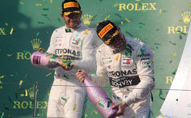 Če že ni mogel prehiteti moštvenega tekmeca Valtterija Bottasa, si je Lewis Hamilton (levo) dal duška pri špricanju šampanjca. FOTO: AFP