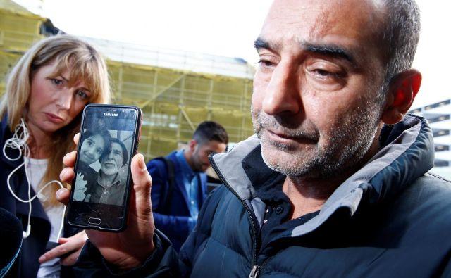 Omar Nabi (na fotografiji) novinarjem govori o svojem očetu (na sliki na telefonu) Daoudu, ki je bil prva identificirana žrtev napadov. FOTO: Edgar Su/Reuters