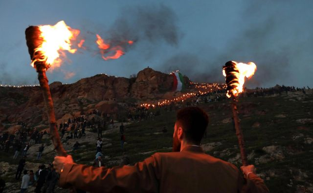 Iraški Kurdi v mestu Akra, 500 kilometrov severno od glavnega mesta Bagdada, prižigajo plamenice med praznovanjem perzijskega novega leta (Noruz). Perzijsko novo leto je starodavna tradicija, ki jo praznujejo Iranci in Kurdi ob spomladanskem enakonočju. FOTO: Safin Hamed/AFP