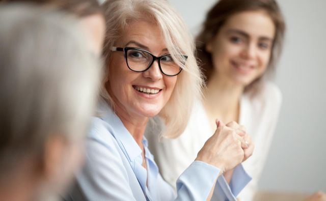 Smiling aged businesswoman in glasses looking at colleague at team meeting, happy attentive female team leader listening to new project idea, coach mentor teacher excited by interesting discussion Foto Fizkes Getty Images/istockphoto