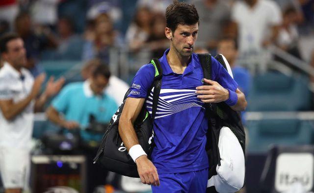 Novak Đoković je z igrišča odkorakal sklonjene glave. FOTO: Julian Finney/AFP