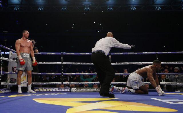 Ukrajinski boksarski šampion Vladimir Kličko (levo) je takole pred dvema letoma v šesti rundi poslal na tla britanskega zvezdnika Anthonyja Joshuo. FOTO: Reuters