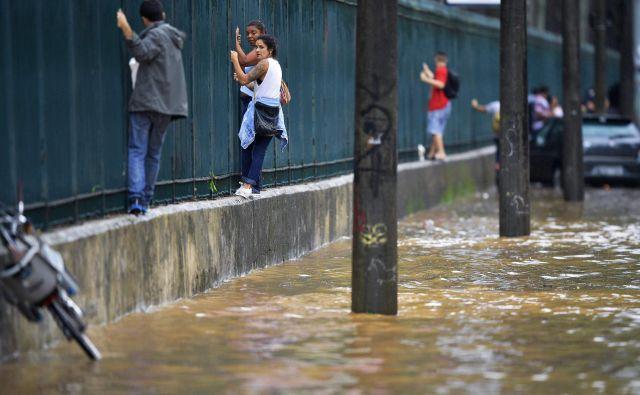 Ljudje plezajo ob ograji, da bi se izognili poplavljenim predelom, ker obstaja možnost, da je voda kontaminirana. FOTO: Carl De Souza/AFP