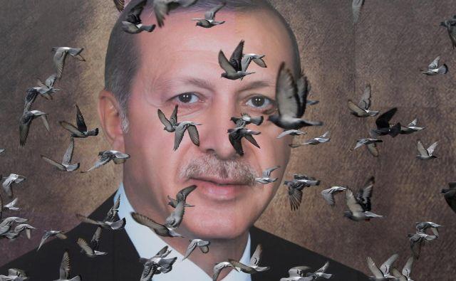 Golobi letijo pred velikanskim plakatom turškega predsednika Erdogana v mestu Bursa.Foto Goran Tomasevic Reuters