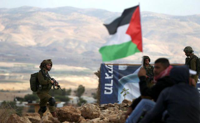 Palestinski protestniki pod budnim očesom izraelskih vojakov v bližini kraja Jeriho na okupiranem Zahodnem bregu, katerega priključitev je med nedavno predvolilno kampanjo napovedal izraelski premier Benjamin Netanjahu. FOTO: Reuters