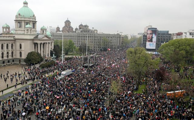 Protest poteka mirno, množica skandira proti predsedniku, ljudje žvižgajo in bobnajo. FOTO: Djordje Kojadinović/Reuters