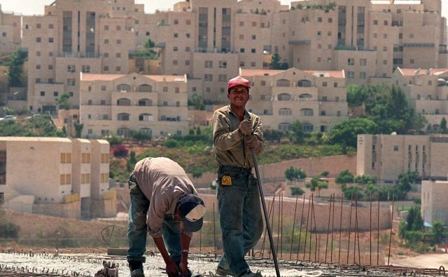Palestinska delavca ob gradnji naselja za judovske priseljence v kraju Ma'ale Adumim na Zahodnem bregu. FOTO: Rula Halawani/Reuters