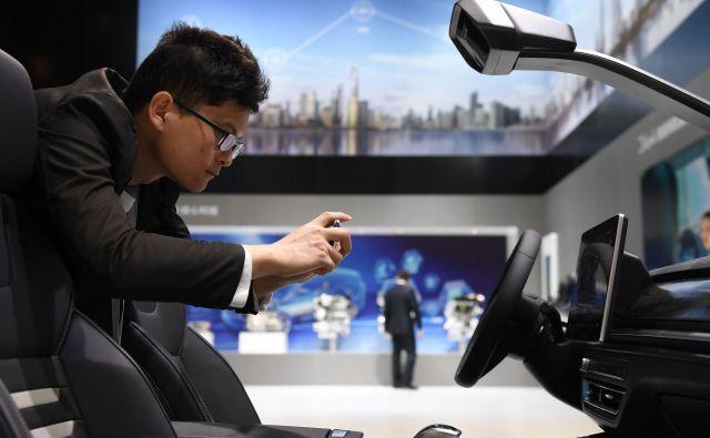 Obiskovalec razstave v Šanghaju si ogleduje notranjost avtomobila kitajske znamke BYD. FOTO: AFP