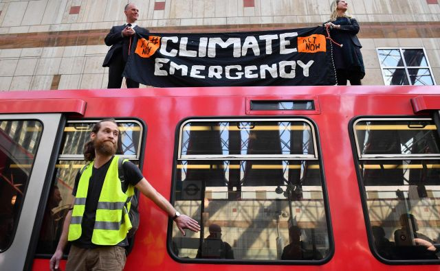 Na današnjem protestu se je moški na sliki s super lepilom prilepil na vrata stoječega vlaka. FOTO: Daniel Leal-olivas/Afp
