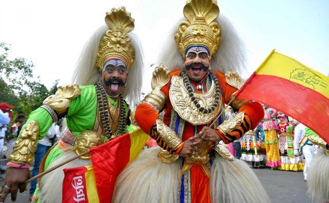 Indijski ljudski umetniki iz Karnatake, oblečeni v božanstva, sodelujejo na shodu med praznovanji na festivalu Mahaveer Jayanthi v Bangaloreju. Foto Manjunath Kiran Afp