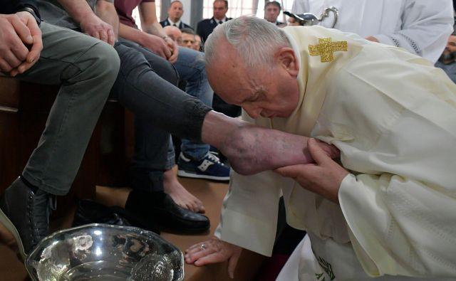 Med obredom je sveti oče nosil predpasnik z napisom: »Ti mi noge umivaš?« FOTO: AFP