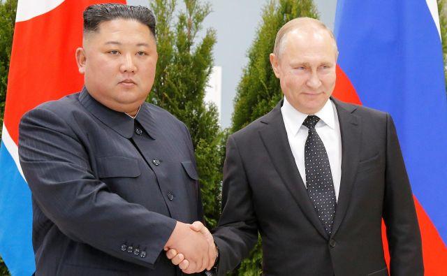Vladimir Putin in Kim Džong Un sta tako pozirala pred številnimi fotografi. FOTO: Aleksander Zemljaničenko/Reuters