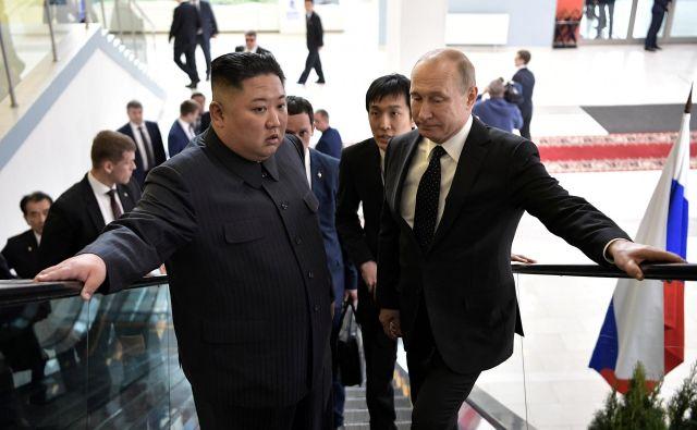 Kim je vedel, da bo vsak njegov stisk Putinove roke pod budnim očesom Donalda Trumpa. FOTO: Reuters