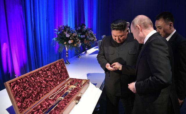 Ruski predsednik Vladimir Putin in severnokorejski voditelj Kim Jong Un si izmenjujeta unikatna darila po zaključenih pogovorih na kampusu vzhodne zvezne univerze v Vladivostoku. Foto Alexey Nikolsky Afp