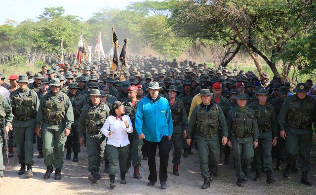 Venezuelski predsednik Maduro hodi ob boku obrambnega ministra in predstavnikov vojske med njegovim obiskom vojaškega oporišča v El Pau. FOTO: Reuters