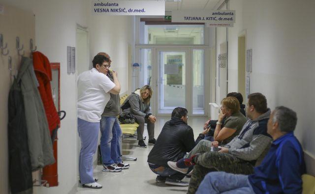 Včeraj je bil hodnik pred ambulantami družinske medicine poln, pacienti so sprijaznjeno čakali, vprašanje je, kako dolgo še. FOTO: Jože Suhadolnik