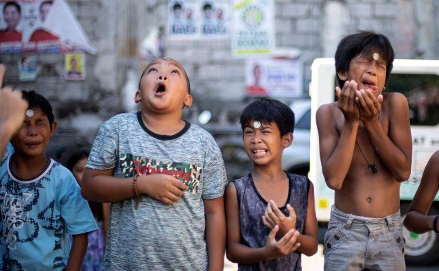 V Manili so se otroci v okviru posta na dan svete Rite iz Casie pomerili v različnih spretnostnih igrah. Na fotografiji so morali kovanec iz čela brez rok kar najhitreje spraviti v usta. Foto Noel Celis Afp