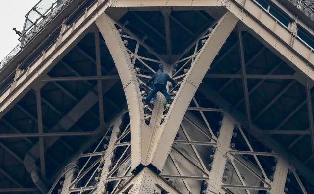 Moški, ki nezavarovano pleza po Eifflovem stolpu. FOTO: Francois Guillot/AFP