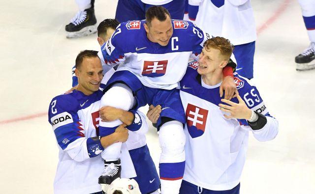 Po zadnji tekmi sta takole Ladislava Nagya z ledu odnesla Andrej Sekera (levo) in Michal Čajkovsky. FOTO AFP