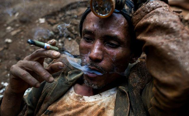 Burmanski rudar med počitkom kadi cigaro v udniku rubinov v Mogoku, severno od Mandalaya. Globoko pod zemljo na tisoče nelegalnih rudarjev ogroža svoja življenja, da bi odkrili bleščeče rdeče dragulje v deželi rubinov. FOTO: Ye Aung Thu/AFP