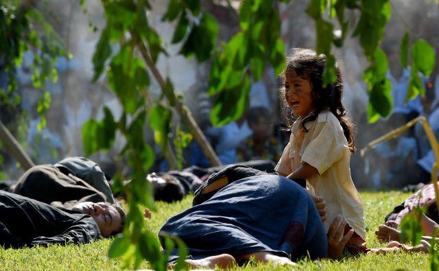 V Kambodji so ob dnevu spomina na žrtve režima Khmerja Rougea, ki je vladal iz leta 1975-79, študenti izvedli protestni performans na poljih Choeung Ek, na katerih je bilo ubitih več tisoč ljudi.FOTO: Tang Chhin Sothy/AFP