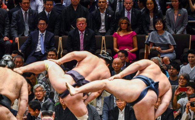 Japonski premier Abe je visokega ameriškega gosta in soprogo Melanio povabil na finale turnirja v sumu. FOTO: AFP