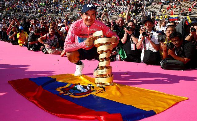 Richard Carapaz se je ponosno postavil ob zmagovalni pokal in ekvadorsko zastavo. Foto Leon Vidic