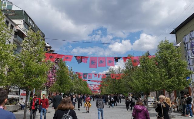 Na Bulevarju matere Terezije v središču Prištine so razobešene izključno albanske zastave, na katerih je na rdečem ozadju upodobljen dvoglavi črni orel. Foto Milena Zupanič