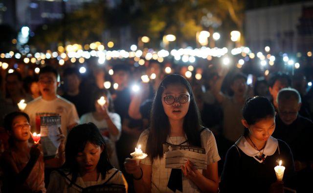 Po podatkih organizatorjev se je jubilejne večerne komemoracije v parku Victoria v Hongkongu udeležilo 180.000 ljudi. FOTO: Tyrone Siu/Reuters