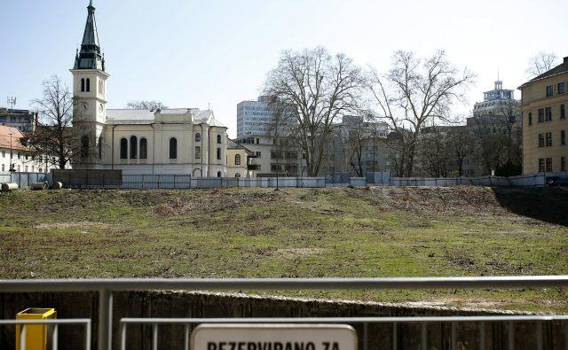 Na že vrsto let ograjenem zemljišču na elitni lokaciji v središču prestolnice gradbenih strojev še ne bomo videli v kratkem. FOTO: Blaž Samec/Delo