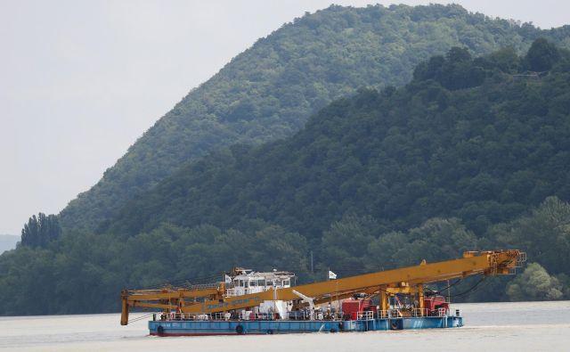 S pomočjo plavajočega žerjava bodo iz reke poskušali izvleči razbitine turistične ladjice. FOTO: Reuters