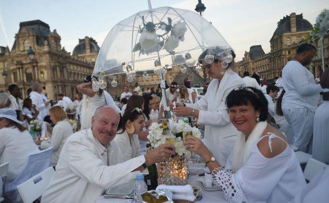 Ljudje, oblečeni v belo, na 31. izdaji prireditve Večerja v belem (Diner en blanc) v Pariških vrtovih Tuileries v Parizu. Prireditev je skrivni stilski fenomen, ki se je začel v Franciji in se razširil po vsem svetu. FOTO: Lucas Barioulet/AFP
