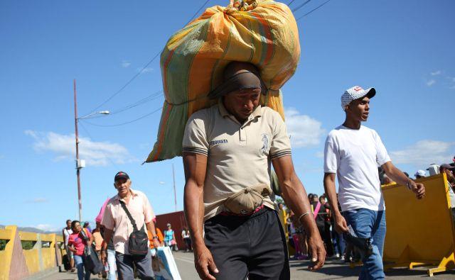 Prebežniki, ki prečajo kolumbijsko-venezuelsko mejo. FOTO: Carlos Eduardo Ramirez/Reuters