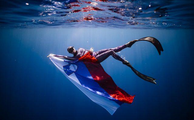 Alenka Artnik gre s slovensko zastavo tudi v morje. FOTO: Dasha Muzykantova