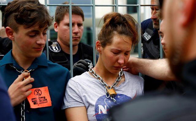 Policisti snemajo verigo okoli vratu podnebnih aktivistov, ki so se protestno priklenili za ograjo pred vlado v Berlinu. FOTO: Fabrizio Bensch/REUTERS