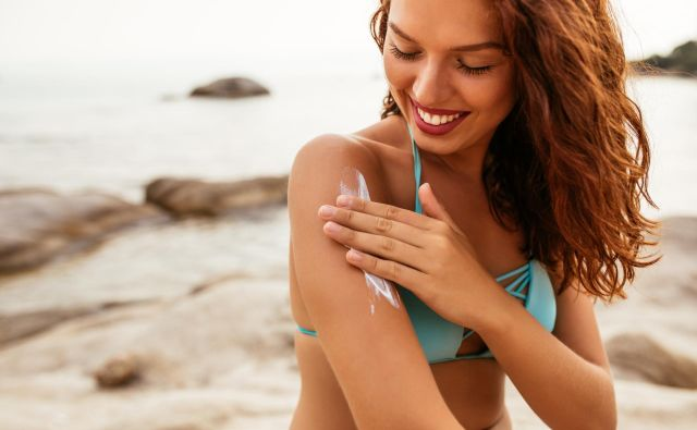 Young woman applying sunscreen lotion on the beach Foto Bernardbodo Getty Images/istockphoto
