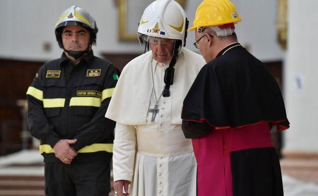 Papež v katedrali v italijanskem mestecu Casemino nosi varnostno čelado. Papež je obiskal območja v škofiji Camerino, ki jih je 24. avgusta 2016 prizadel potres.FOTO: Handout/AFP
