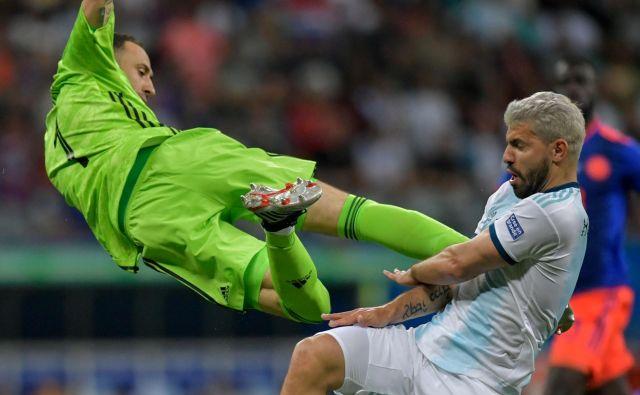 Na južnoameriškem nogometnem prvenstvu je v skupini B v vodstvu Kolumbija, ki je v soboto z 2:0 premagala Argentino. Na fotografiji je kolumbijski vratar David Ospina trčil v argentinskega napadalca Sergia Aguera.FOTO: Raul Arboleda/AFP