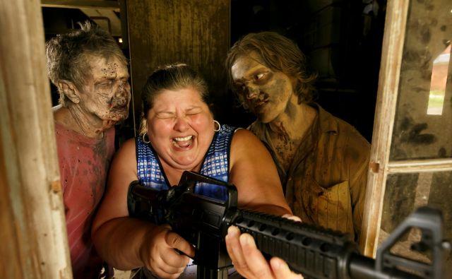 V filmski produkcijski hiši AMC v ameriški zvezni državi Georgia, kjer snemajo tretjo sezono nadaljevanke Hodeči mrtveci (The Walking Dead), za turiste organizirajo nenavadno izkušnjo na snemalnih lokacijah. Da je izkušnja turistom še bolj pristna so poskrbeli tudi za hodeče mrtvece, ki turiste strašijo in jih lovijo. FOTO: Christopher Aluka Berry/REUTERS