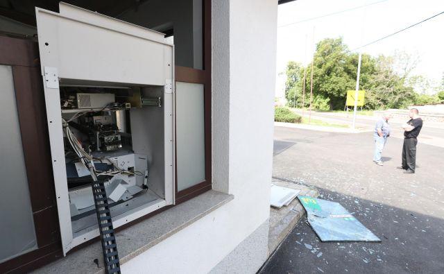 Policisti so ugotovili, da so neznani storilci z eksplozijo poškodovali bankomat in iz njega ukradli za zdaj še neznano količino denarja. FOTO: Dejan Javornik