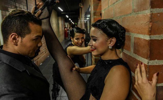 V kolumbijskem Medelinu od 16. do 24. junija poteka mednarodni festival tanga XIII International Tango Festival, del katerega je tudi plesno tekmovanje. Na fotografiji se par v zaodrju pripravlja na nastop. FOTO: Joaquin Sarmiento/AFP