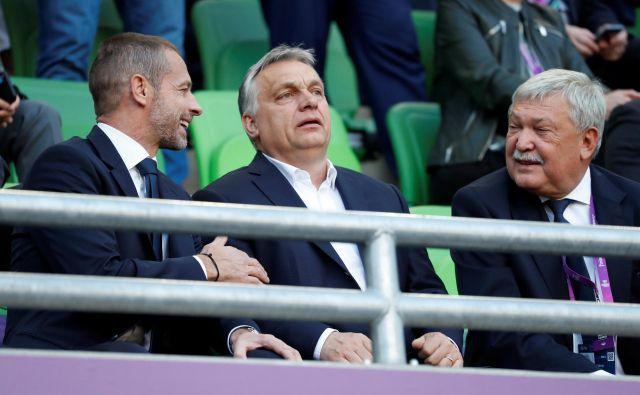 Prvi človek banke OTP in madžarske nogometne zveze Sándor Csányi (desno) na nogometni tekmi skupaj z madžarskim premierom Viktorjem Orbanom (v sredini) in predsednikom Uefe Aleksandrom Čeferinom. Foto Reuters