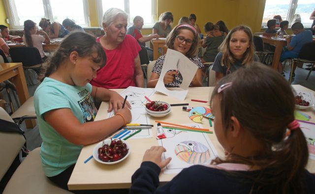 Stanovalci mariborskega doma Danice Vogrinec in otroci se skupaj igrajo miselne igre, rišejo, pojejo in si pripovedujejo zgodbe. Foto Tadej Regent