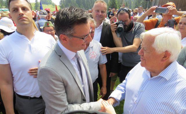 Tovariški stisk rok predsednika vlade Marjana Šarca in prvega predsednika Slovenije Milana Kučana. FOTO: Bojan Rajšek/Delo