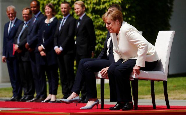 Angela Merkel je včeraj z dansko premierko Mette Frederiksen himno poslušala sedé. To je huda kršitev protokola, so pisali svetovni mediji. FOTO: Reuters
